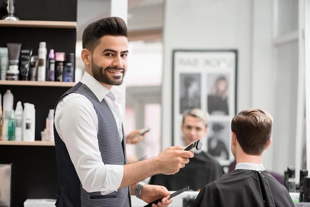 Barbeiro de sorriso que faz hairdress para o cliente novo no barbeiro. Foto Premium