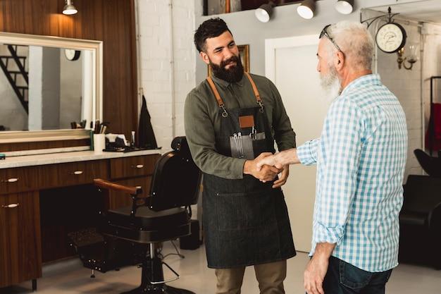 Barbeiro e cliente masculino sênior, apertando as mãos Foto gratuita