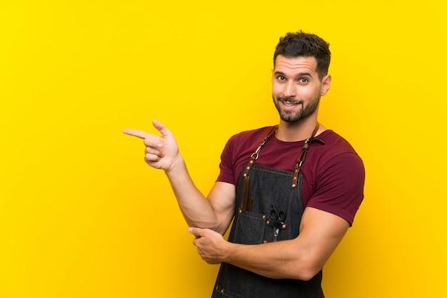 Barbeiro em um avental apontando o dedo para o lado Foto Premium