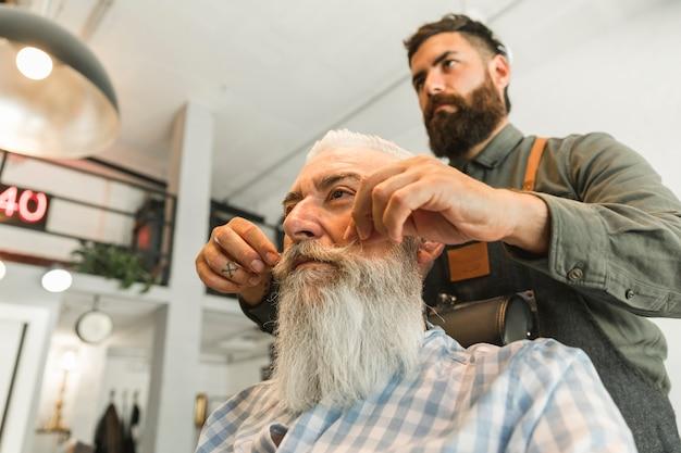 Barbeiro endireitar bigode de cliente sênior Foto gratuita