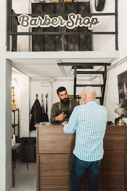 Barbeiro, falando, com, cliente, em, escrivaninha recepção Foto gratuita