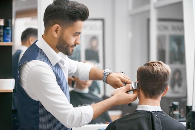 Barbeiro fazendo novo corte de cabelo para cliente jovem sentado na frente do espelho. Foto Premium