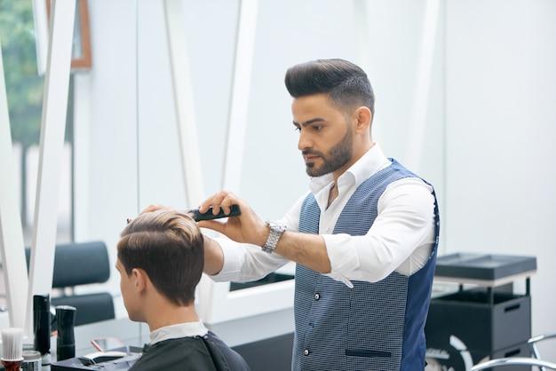 Barbeiro fazendo novo corte de cabelo para cliente jovem. Foto Premium