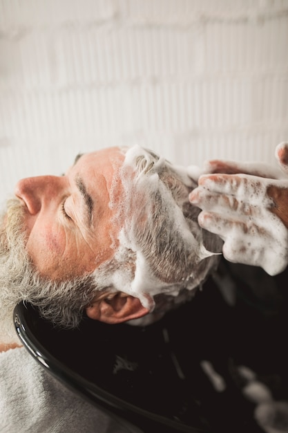 Barbeiro, mãos, e, macho velho, cliente, shampooed, cabeça Foto gratuita