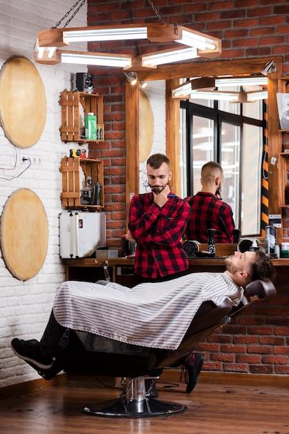 Barbeiro pensando em um penteado para o cliente Foto gratuita