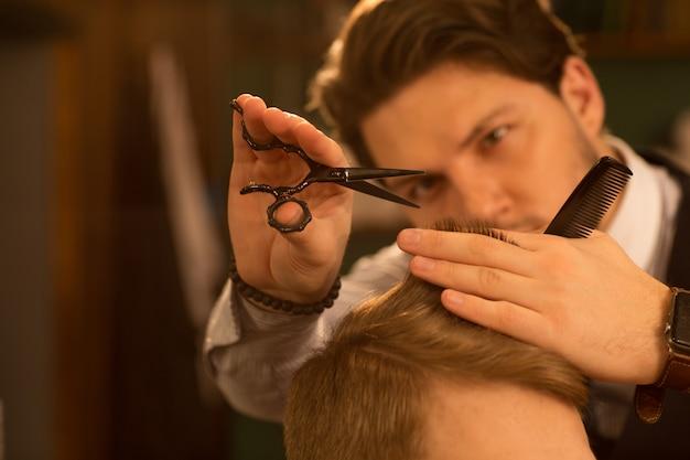 Barbeiro profissional trabalhando em sua barbearia Foto Premium