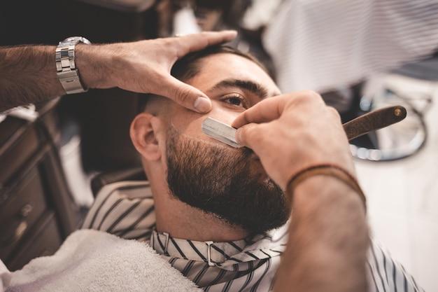 Barbeiro raspa a barba do cliente Foto Premium