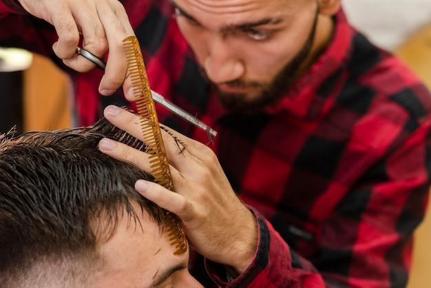 Barbeiro, usando uma tesoura e pente para cabelo Foto gratuita