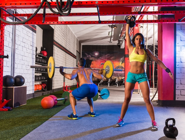 Barbell levantamento de peso homem mulher subindo kettlebell Foto Premium