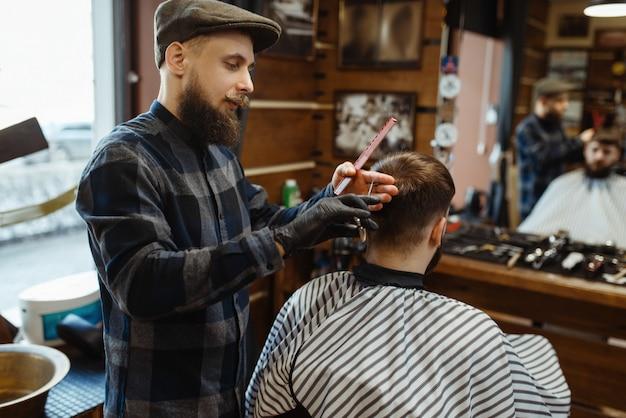 Barber faz um corte de cabelo para cliente, barbearia Foto Premium