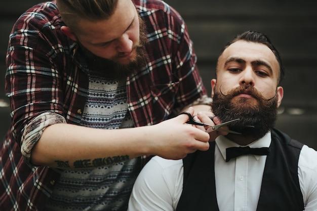 Barber usando uma tesoura para retocar uma barba Foto gratuita