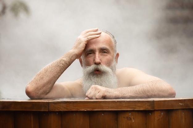 Barbudo homem sênior desfrutando de banho termal no centro de talassoterapia. Foto Premium