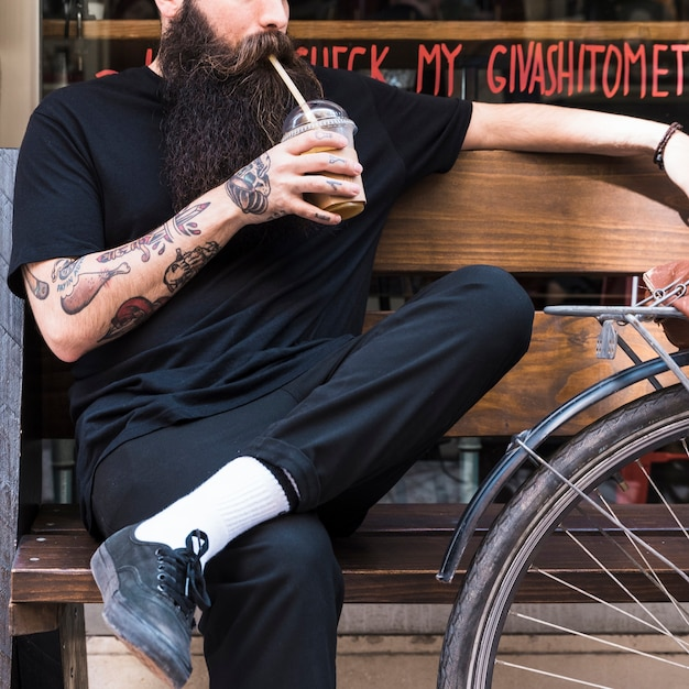 Barbudo jovem bebendo o milk-shake de chocolate sentado no banco Foto gratuita