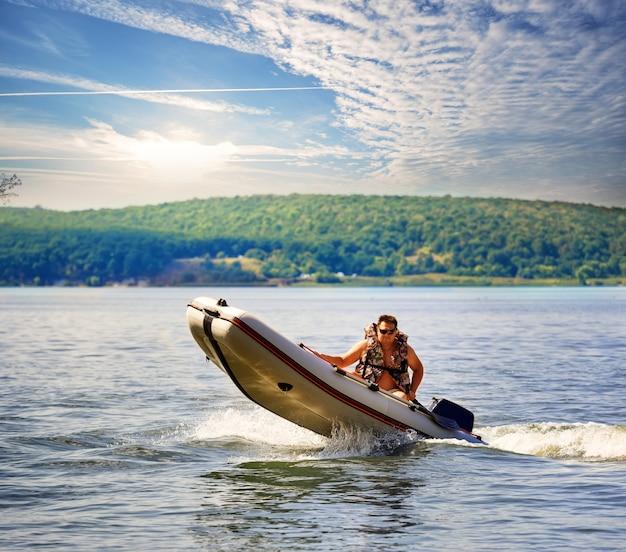 Barco a motor inflável com homem em colete salva-vidas Foto Premium