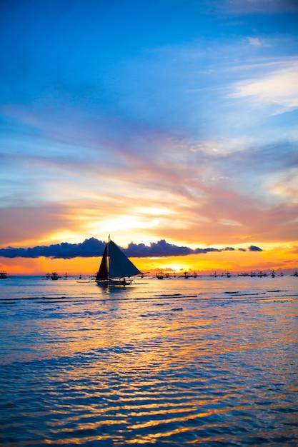 Barco à vela no pôr do sol incrível na ilha de boracay Foto Premium