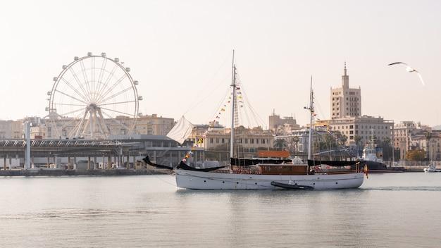 Barco atravessando o porto de málaga com a roda gigante ao fundo Foto Premium