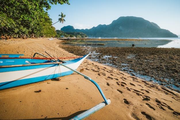 Barco bangka banca na praia remota iluminada pela luz dourada do sol. aldeia de el nido. filipinas. Foto Premium
