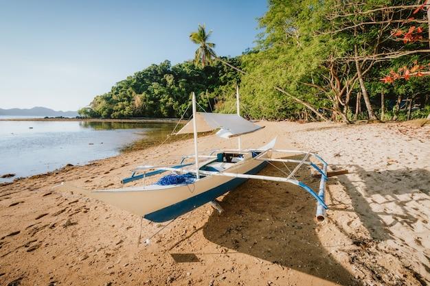 Barco bangka na praia remota com luz dourada do sol. baía de el nido. filipinas. Foto Premium