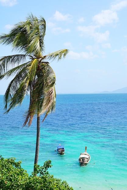 Barco de cauda longa e céu azul no paraíso com água cristalina bonita na ilha de phi phi Foto Premium