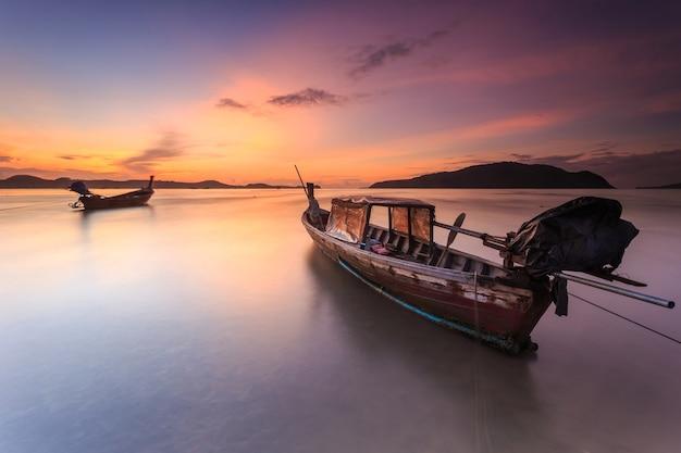Barco de cauda longa tailandesa tradicional e belo nascer do sol no mar em phuket, tailândia Foto Premium