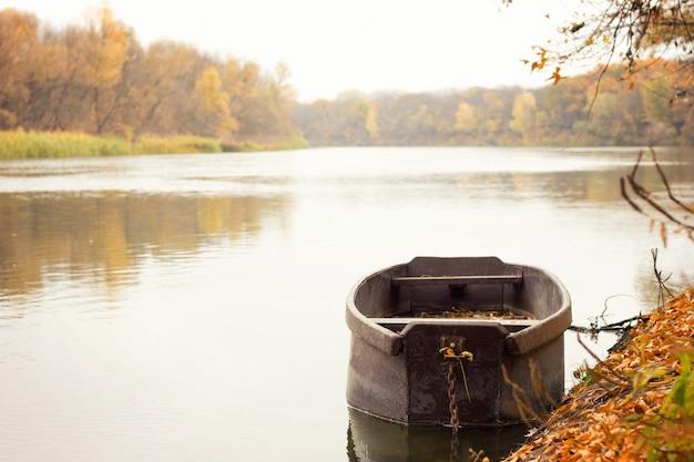 Barco de madeira no rio, paisagem de outono, com um lugar sob a inscrição Foto Premium