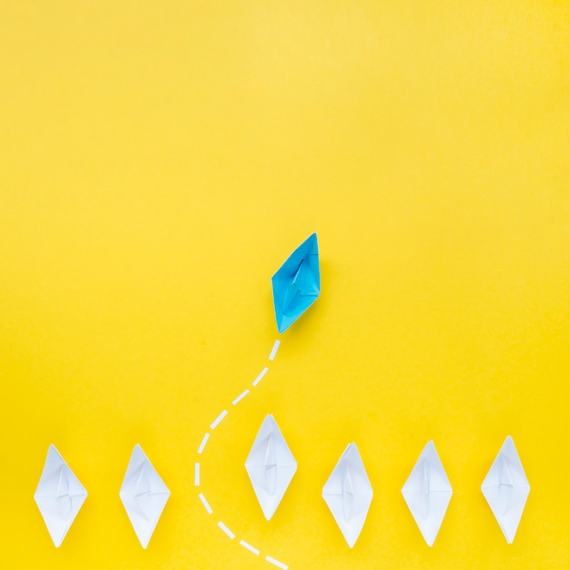 Barco de papel azul na frente de barcos de papel branco Foto Premium