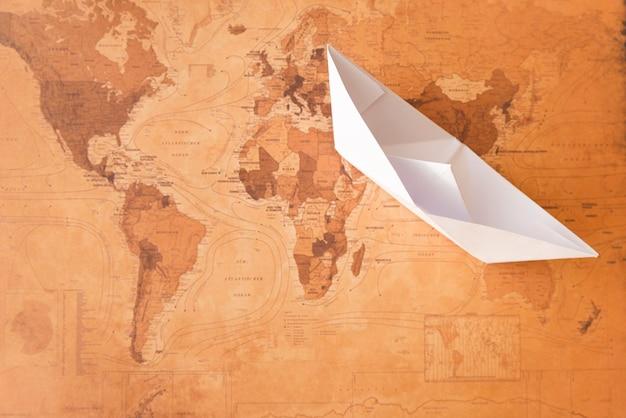 Barco de papel no mapa sépia Foto gratuita