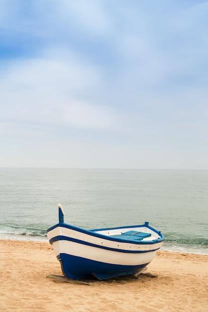 Barco de pesca de madeira em uma praia arenosa Foto Premium