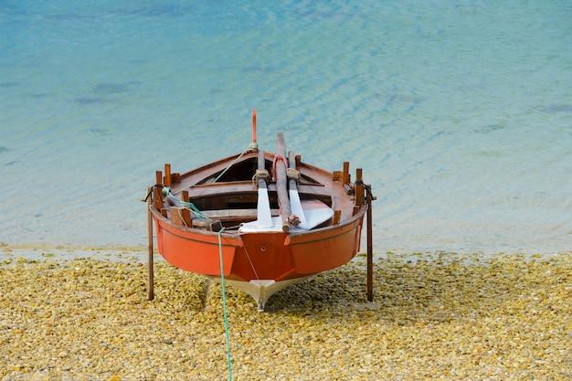 Barco de pesca de madeira seca na praia Foto Premium