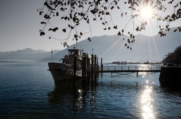 Barco de pesca em um lago alpino com belos raios de sol na suíça Foto gratuita