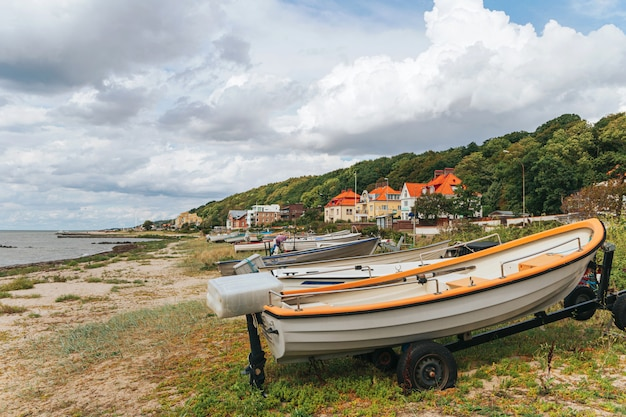 Barco de pesca na praia, barco na costa do mar, barco a remo velho na praia. Foto Premium