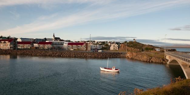 Barco de pesca no rio, ao lado da cidade e ponte Foto Premium