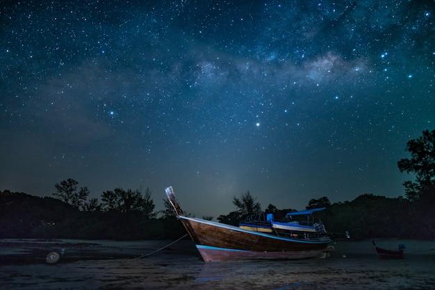Barco de viagem na praia com estrela cintilante Foto Premium