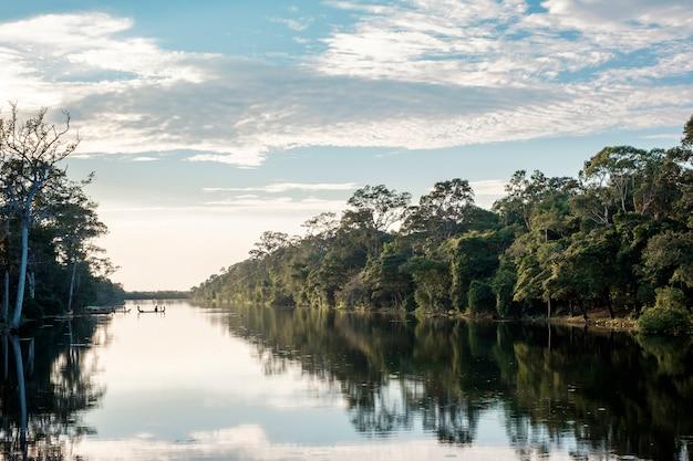 Barco, floresta, rio e céu azul na reflexão Foto gratuita
