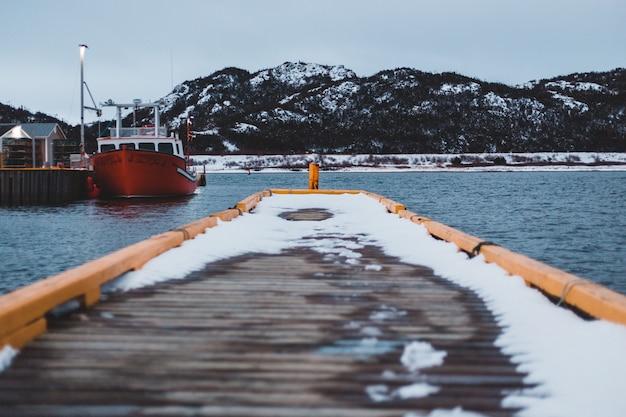 Barco laranja no corpo de água, vendo a montanha Foto gratuita