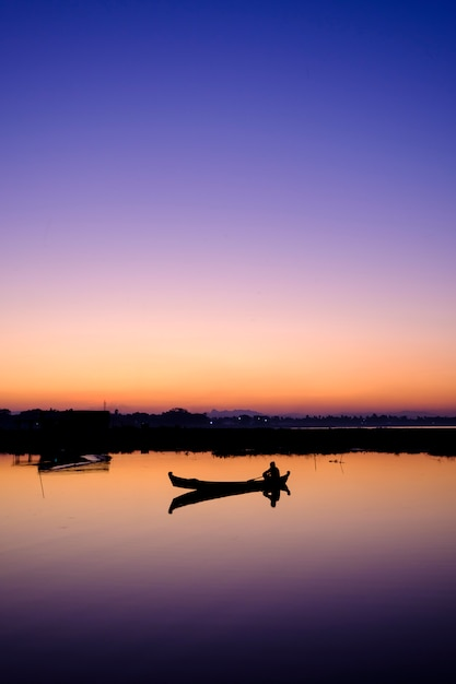 Barco no pôr do sol no lago Foto gratuita
