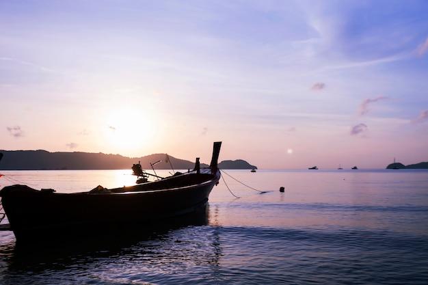 Barco ou longtail barco no mar no tempo de manhã com belo nascer do sol e reflexão em Foto Premium