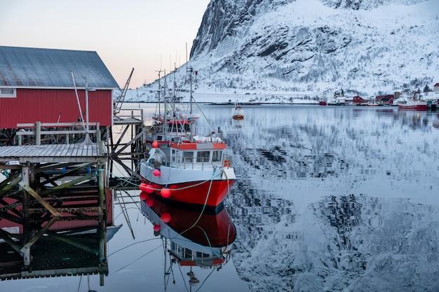 Barco pesca, escorado, ligado, cais, com, vermelho, vila, em, lofoten, ilhas Foto Premium