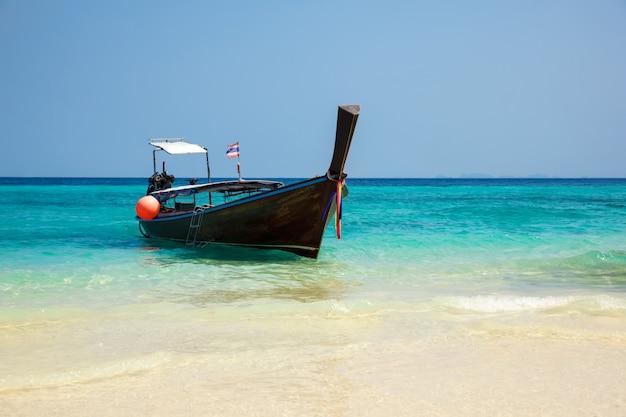 Barco tradicional longtail na praia tropical perto da ilha de koh phi phi, tailândia Foto Premium