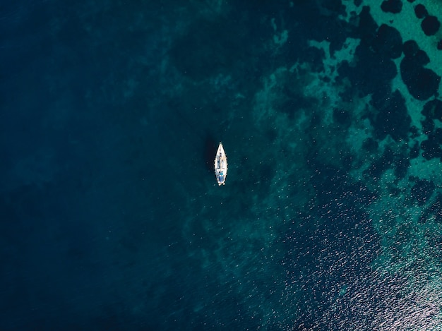 Barco único no meio de um mar azul claro Foto gratuita