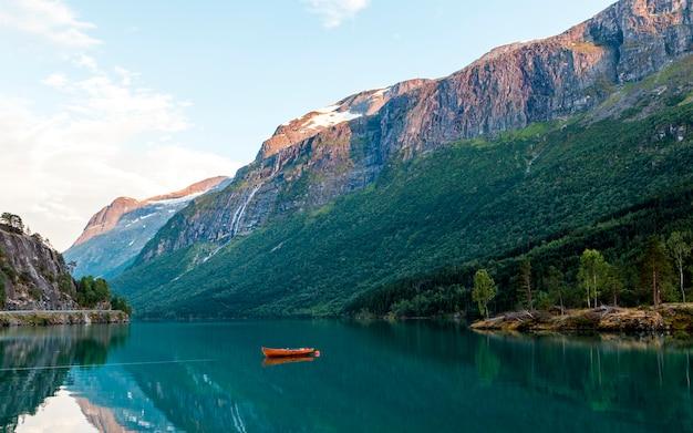 Barco vermelho atracado no lago idílico perto das montanhas rochosas Foto gratuita