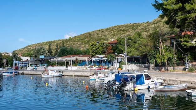 Barcos atracados na água perto da rua de aterro com edifícios e restaurantes, muito verde, colinas verdes, grécia Foto gratuita