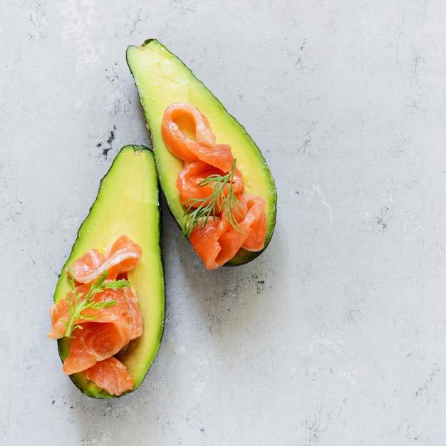 Barcos de abacate maduros com fatias de truta salgada, salmão e verduras frescas. barcos de abacate recheados com salmão com limão, folhas de espinafre e rúcula, comida saudável de conceito, dieta. Foto Premium