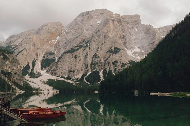 Barcos de madeira no lago somwhere nas dolomitas italianas Foto gratuita