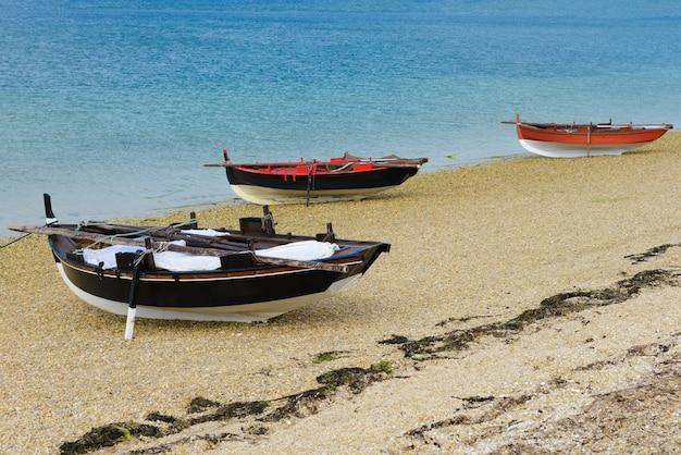Barcos de pesca de madeira secam na praia Foto Premium