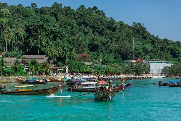 Barcos de pesca tailandeses tradicionais embrulhados com fitas coloridas. no contexto de uma ilha tropical. Foto Premium