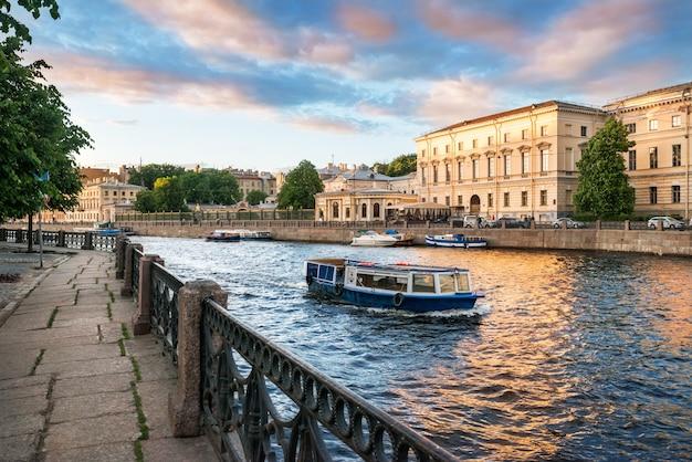 Barcos de recreio no rio fontanka em são petersburgo em uma noite ensolarada e o dique Foto Premium