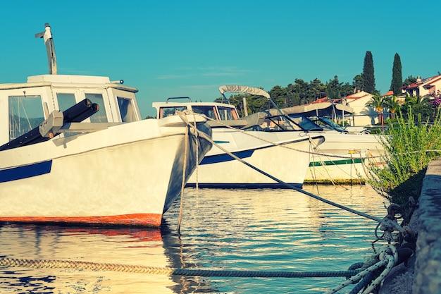 Barcos e casas na vila de vrboska, ilha de hvar, dalmácia, croácia, europa. transporte marítimo de verão tonificado. Foto Premium