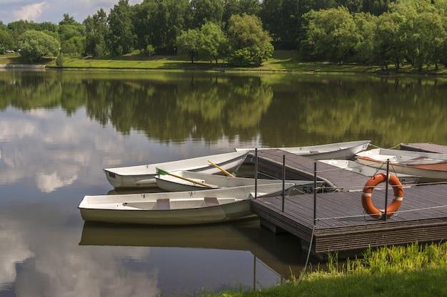 Barcos no cais em um rio pequeno. a linha da vida está pendurada na doca Foto Premium