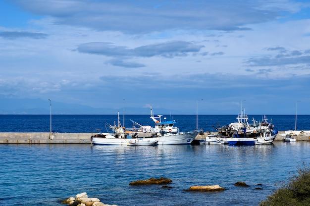 Barcos no porto de nea roda na água do mar azul, halkidiki, grécia Foto Premium